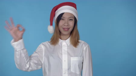 çok güzel : young asian woman posing wearing santa claus hat showing symbol hand gesture ok on blue background in studio. attractive millennial girl wearing white casual shirt looking at the camera laughing