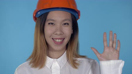 hat : close up portrait young asian architect waving hand say hello wearing orange hard hat on blue background in studio. attractive millennial girl looking at the camera Stock mozgókép