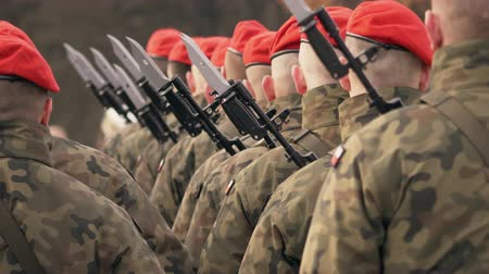 commando : Soldiers in red berets and military uniforms stand with their guns against their backs to the camera. Only the back of the soldiers are visible.