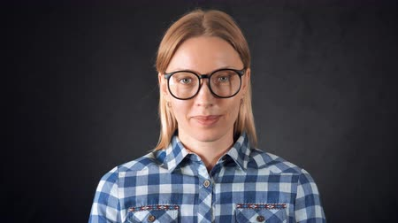ношение : portrait adult candid woman with blond hair on black background. smart girl wearing eyeglasses casual bright shirt looking at the camera Стоковые видеозаписи