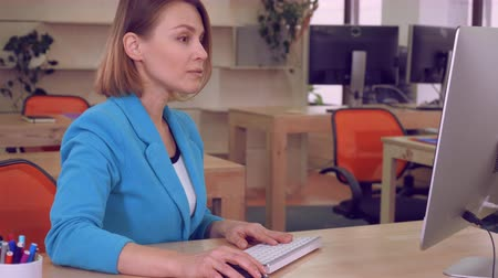 удачливый : successful businesswoman in the office. caucasian adult manager working with computer looking on screen display. happy elegant entrepreneur celebrating win at work Стоковые видеозаписи