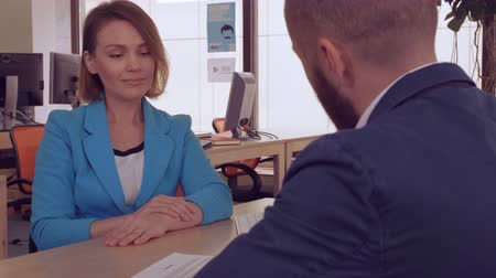 занятость : candid woman manager in bank giving document with cheerful smile client signing contract. business people shaking hands in modern office after great deal. meeting with estate agent