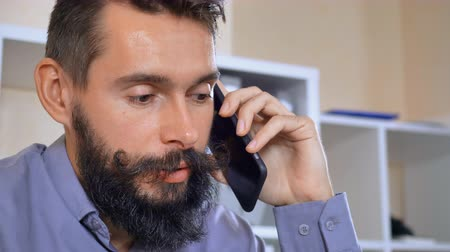 dizer : portrait handsome man with beard and mustache has phone conversation. young businessman wearing casual shirt using smartphone talking with client or friend at home office