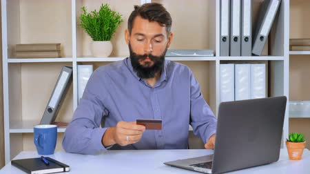 bakalář : trendy millennial using app for booking and pay ticket or checking state of an account. guy with beard and mustache wearing casual blue shirt sitting at the desk in modern office Dostupné videozáznamy