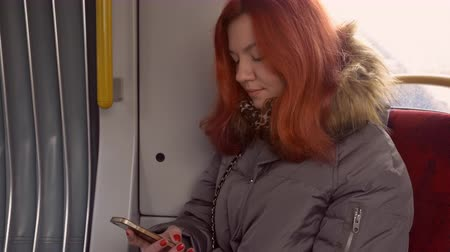 рыжеволосый : young redhead woman sitting on the seat in tram. beautiful girl with red long hair using smartphone messaging or use application mobile phone wearing winter jacket