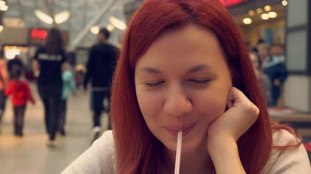 ruivo : portrait beautiful woman with long red hair in cafe. attractive ginger girl relish drink looking at the camera with friendly smile resting in shopping center Stock Footage