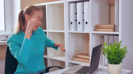 victorious : worker dancing victorious dance at work. caucasian young employee have fun in small office with white furniture. attractive funny woman with blonde hair wearing casual shirt