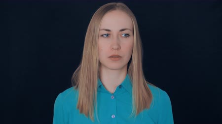 caráter : portrait beautiful caucasian woman with blonde hair posing in studio on black background. young girl wearing turquoise shirt showing hand gesture bingo