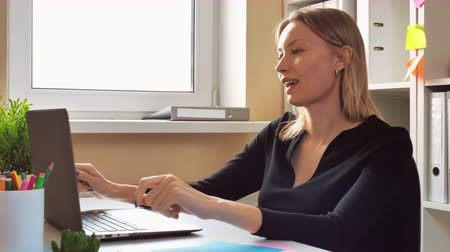 victorious : adult woman resting at the workspace. caucasian entrepreneur dancing in the small office. female with blond hair wearing black dress listening tranquil music sitting at the desk in room with window