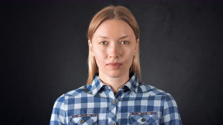 плечо : portrait young caucasian woman with blond hair posing on black background. attractive girl wearing casual bright shirt looking at the camera with friendly smile showing sign have idea Стоковые видеозаписи