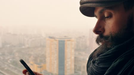 megalopolis : close up face handsome man with beard and mustache using smartphone outdoors. handsome trendy guy standing in the balcony in winter season texting message urban landscape