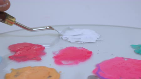 pinky : Different color stains on the palette of an artist. Pinky shades, white, yellow and turquoise colors.