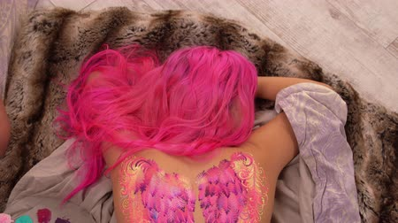 fuksja : Lady with pink hair is modelling. Artwork on her body is almost finished.