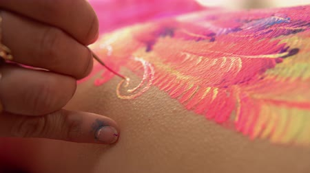 fuchsie : Drawing wings with traditional ornament. Model laying as canvas.