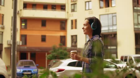 wearing earphones : woman passing parking lot in residential quarter. she listening to the audio book in her headphones.
