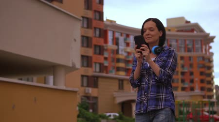 wearing earphones : woman is typing a message while walks in modern district of the city. she is wearing purple shirt and blue jeans. Stock Footage