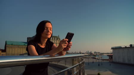 ограждение : brunette woman using her mobile phone with city landscape background. elegant lady leaned against metallic enclosure. Стоковые видеозаписи