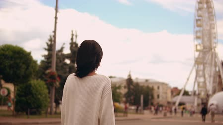 shaking wind : lady wearing white sweater walks through the market square. her hair is fluttering on the wind. Stock Footage