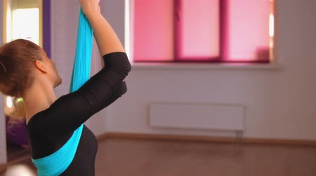 melegítőben : woman is twisting doing aerial yoga training. she trains her back muscles.