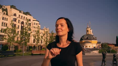 paving : lady fixing her hairstyle. she is walking along the beautiful street. Stock Footage