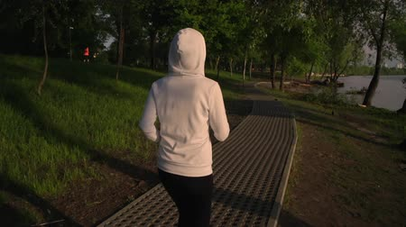 улица : back view woman running at sunrise. fit female wearing bright sneakers and white hoodie run alone in park. beautiful nature landscape sunlight