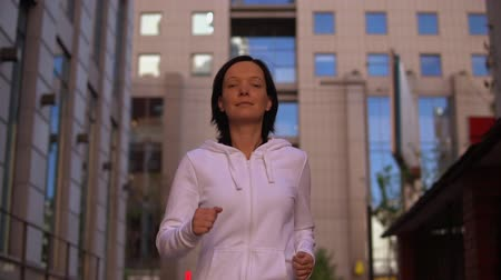 megalopolis : portrait woman running in modern urban city slow motion. caucasian girl wearing white hoodie looking at camera enjoys jogging and loneliness. on background cityscape