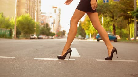 high heeled shoe : Close up details female legs wearing high-heels shoes walking on the road in urban modern city. slow motion