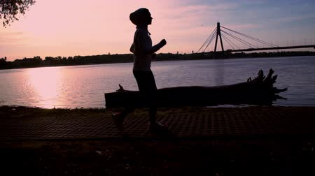 buldog : girl jogging along the river in the evening slow motion. woman enjoy running at sunset. amazing landscape setting sun in the blue sky and river. active healthy feminine lifestyle