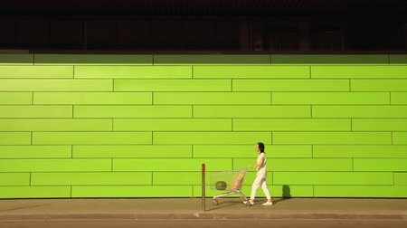 potraviny : woman walking along green wall. female carries a shopping cart with purchases. Lady wearing white casual jeans and t-shirt goes on parking of a supermarket.