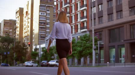 arka görünüm : Back view woman walking along the road in morning town. businesswoman wearing elegant white shirt and skirt. Urban city view in summer season. slow motion