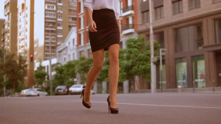 high heeled shoe : Close up female legs walking along the sidewalk. unrecognizable business woman wearing black skirt and high-heeled shoes. on the background urban city landscape. slow motion Stock Footage