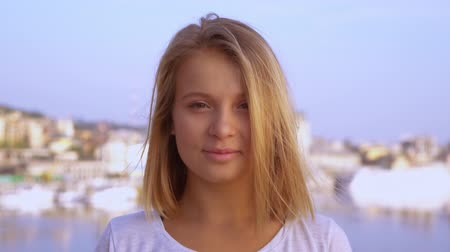 přímý : girl looks directly into the camera and smiles. close-up of a blonde womans face.