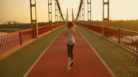 fones de ouvido : lady runs during the sunset. blonde female wearing black and white sportswear.