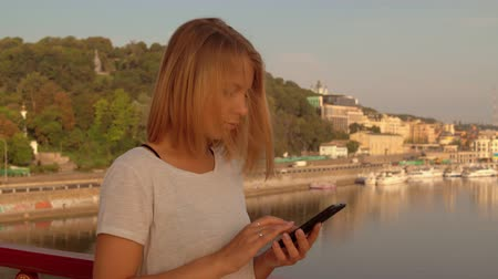 waterline : blonde woman using her mobile phone. lady wears white t-shirt.