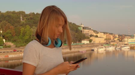 waterline : lady typing a message wearing blue headphones. female wears white t-shirt.