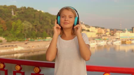 wearing earphones : lady wearing blue headphones. female blonde enjoying music.