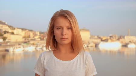 přímý : blonde female standing by the riverside. lady wears white t-shirt.