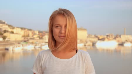 přímý : lady is wearing white t-shirt. female standing with seaside at the background. Dostupné videozáznamy