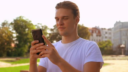 sending : young caucasian man walking using smartphone. handsome businessman texting message on mobile outdoors