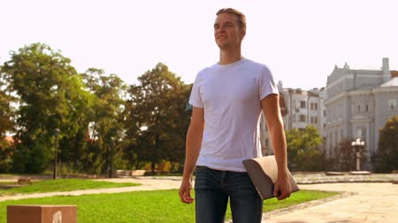 goes : young caucasian businessman holding laptop walking on the street. trendy man wearing casual t-shirt going with happy smile