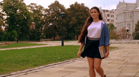 learning to walk : caucasian woman walks to class holding book and notebook. girl with long hair wearing casual shirt and skirt slow motion