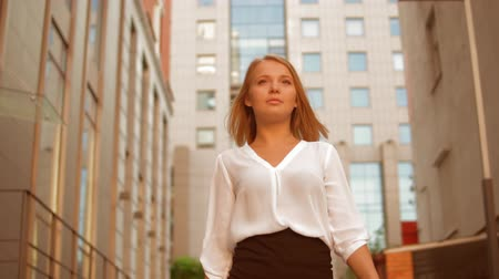 goes : young businesswoman walking along business building. Happy white collar worker walks on the street in city center. slow motion Stock Footage
