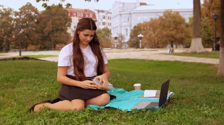 нетбук : businesswoman eating sandwich sitting under the tree young brunette working typing on laptop Стоковые видеозаписи
