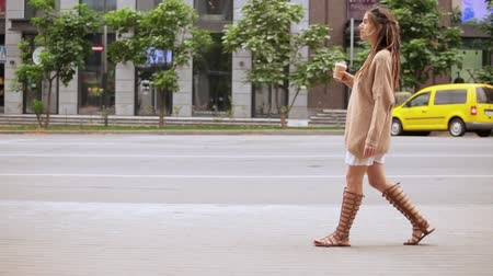 идентичность : young hipster woman walking along the road drinking coffee to go. caucasian model with dreadlocks wearing trendy sweater slow motion millennial lifestyle