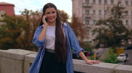 daily life : happy young woman has phone conversation outdoors. girl wearing denim t-shirt using smartphone Stock Footage