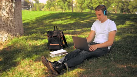 anız : caucasian guy sitting on the lawn in park using laptop. happy student has break listening music Stok Video