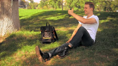facetime : young caucasian man has video call with friend sitting on the lawn in park. guy chatting online outdoors