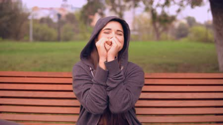 sinais : young woman showing sign love wearing casual hoodie sitting on the bench in park looking at the camera with friendly smile.