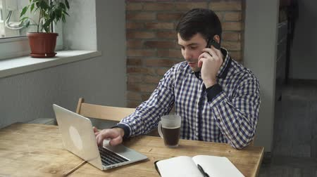 use laptop : young businessman sitting at the working place typing on laptop talking by phone with client. candid guy has negotiation