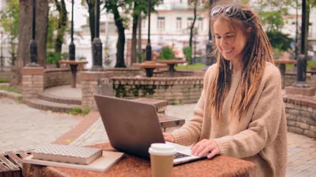 hızlandırmak : young caucasian woman with dreadlocks has video call with friend sitting in autumn park. Happy freelancer using webcam on laptop Stok Video